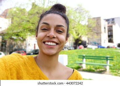 Close up portrait of cheerful young african woman standing outdoors and taking selfie