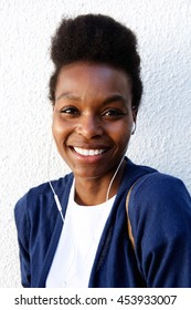 Close up portrait of cheerful young african woman with earphones listening to music against white background