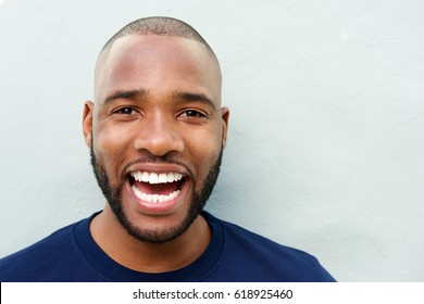Close up portrait of cheerful young african man laughing against white wall