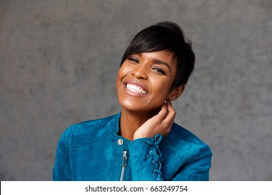 Close up portrait of cheerful young black woman against gray background