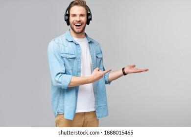 Nahaufnahme eines Porträts von fröhlichen jungen Männern, die Musik hören, die eine lockere Jeans-Ausstattung trägt