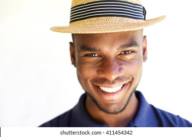 Close up portrait of cheerful young man in hat against white background