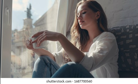 Close up portrait of cheerful young woman with frizzy hair sitting in the room enjoying a cup of tea and looking through the window at the city