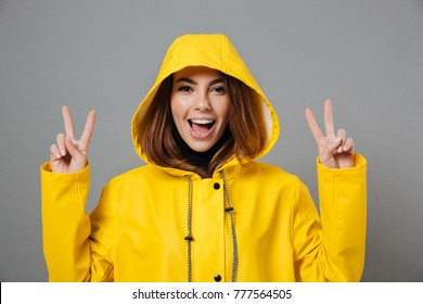 Close up portrait of a cheery girl dressed in raincoat posing with hood on her head and showing peace gesture isolated over gray background