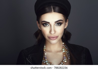 Close up portrait of chic glam dark-haired model with beautiful make up and smooth hair wearing black pillbox hat, leather jacket on naked body and luxurious gem necklace. Isolated on grey background