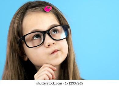 Close up portrait of a child school girl wearing looking glasses holding hand to her face thinking about something isolated on blue background.