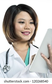 Close up portrait of a Chinese Female doctor using a digital tablet & wearing a lab coat plus stethoscope.