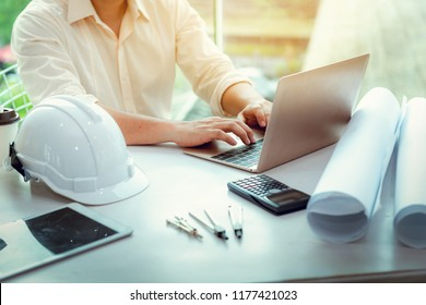 Close up portrait of civil engineer using laptop to  planning project schedule., Engineering and construction concept.