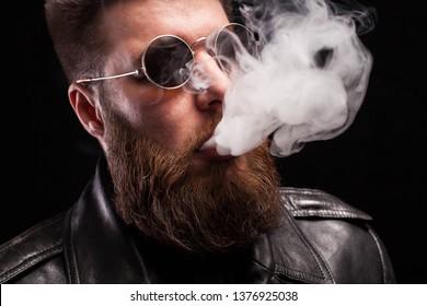 Close up portrait of confident bearded man wearing black leather jacket and sunglases smoking electronic cigarette over black background. Stylish man. Dramatic portrait.