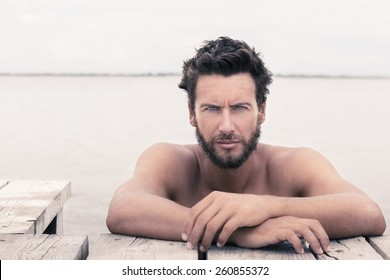 Close up Portrait of Confident Gorgeous Handsome Man with No Shirt Posing at the Sea