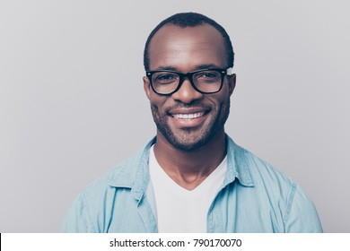 Close up portrait of confident handsome clever cheerful joyful university professor wearing casual denim jeans shirt and black rim-glasses, isolated on gray background