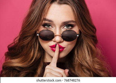 Close up portrait of a confident pretty girl wearing sunglasses showing silence gesture with finger over her lips isolated over pink background