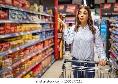 Close up portrait of a confused casual woman peeking out from the aisle in a supermarket and deciding what to buy. Confused young woman looking at supermarket shelves