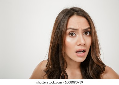 Close up portrait of confused caucasian woman looking on camera in puzzlement with facial expressions isolated over white background