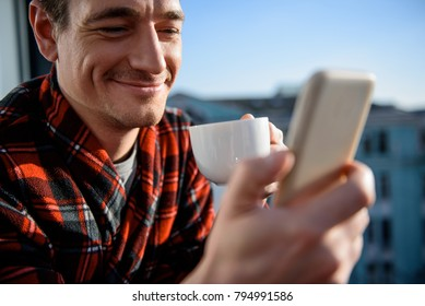 Close up portrait of contented guy looking at mobile phone with smile. He is having a cup of coffee and standing outside. Focus on his face