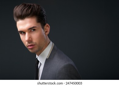 Close up portrait of a cool guy modern hairstyle posing on gray background