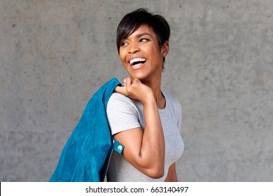 Close up portrait of cool young black woman laughing with blue jacket against gray wall