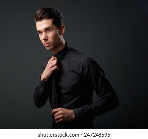 Close up portrait of a cool young man in black shirt and tie