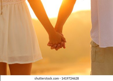 Close up portrait of a couple holding hands walking at sunset