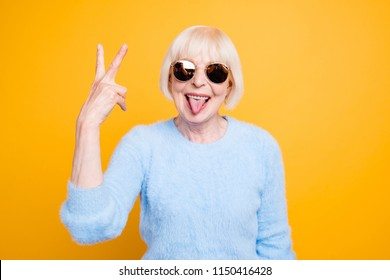 Close up portrait of crazy modern grandma stuck out her tongue and showing v-sign isolated on yellow background