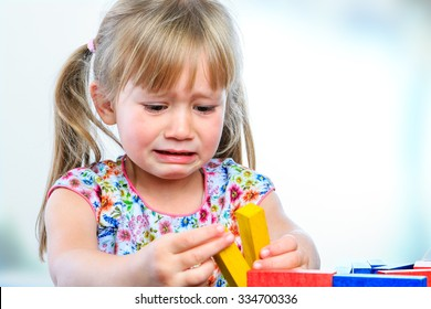 Close up portrait of crying little girl playing with wooden blocks at table.Frustrated girl showing moody behavior and long face.