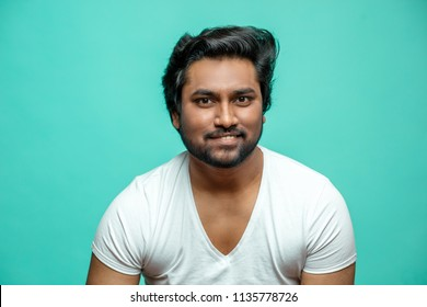 close up portrait of cunning Indian male pretending that he is smiling.Hindoo guy is smiling to show sarcasm. derisive face. quizzical look
