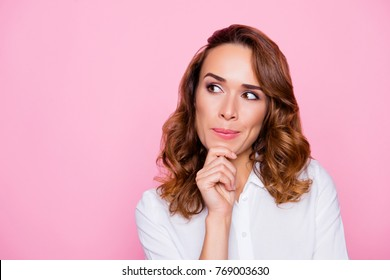 Close up portrait of curious cheerful charming attractive woman with ideal hairdo and make up, she is thinking about the right choice and touching chin, isolated on bright pink background, copyspace