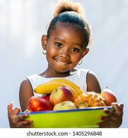 Close up portrait of cute African girl holding fruit bowl.Isolated against light background.
