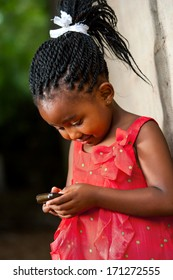 Close up portrait of cute african girl with braided hair playing on smart phone.