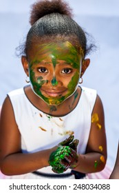 Close up portrait of cute African girl with painted face at painting session.Isolated against light background.