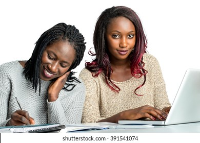 Close up portrait of cute african teen students doing homework together.Girl with braided hair writing with pen on notebook and girl with reddish hair typing on laptop.Isolated on white background.