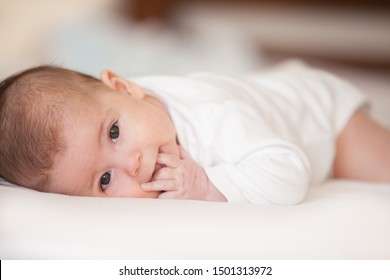 Close up portrait of cute baby. Adorable baby lay on white matress in white bedroom. Family morning at home. Child relaxing on white bed. Textile and bedding for kids. Kid looking into the camera