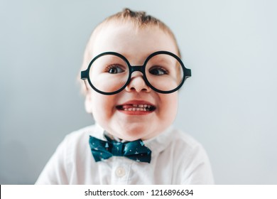 Close up portrait of cute baby boy wearing smart outfit and eyeglasses, smiling and showing his tongue at the camera. Kids fashion concept.