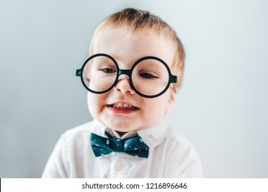 Close up portrait of cute baby boy wearing smart outfit and eyeglasses and smiling at the camera. Kids fashion concept.