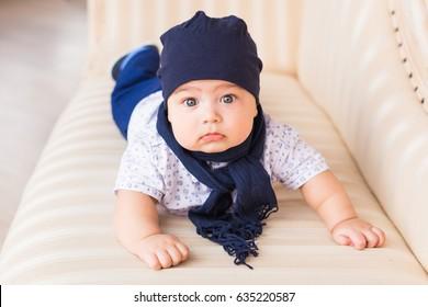 Close up portrait of cute baby boy wearing blue hat.