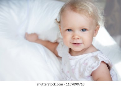 Close up portrait of a cute baby girl with big beautiful blue eyes and with blonde curly hair relaxing on a white blanket. Little girl 1 year old.