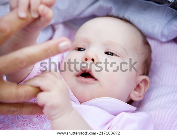 Close up portrait of a cute baby girl holding parent hands