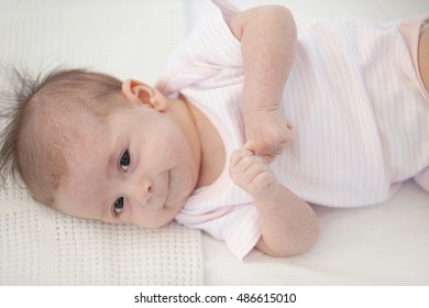 Close up portrait of cute baby. Little baby lying on a white bed. Family morning at home. Child relaxing on white bed. Textile and bedding for kids. Kid looking into the camera