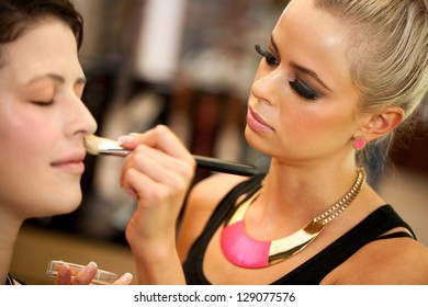 Close up portrait of cute blond make up artist applying color on face.