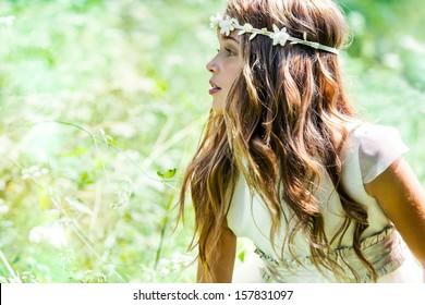 Close up portrait of cute girl in green field.