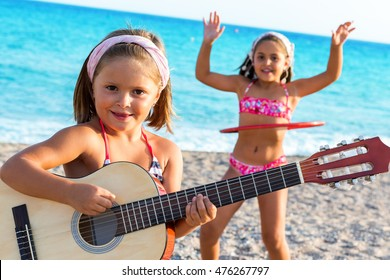 Close up portrait of cute girl playing guitar on beach with friend dancing in background.