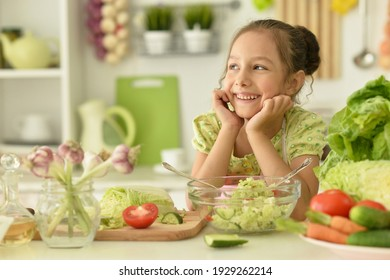 Close up portrait of cute girl preparing delicious fresh salad in kitchen