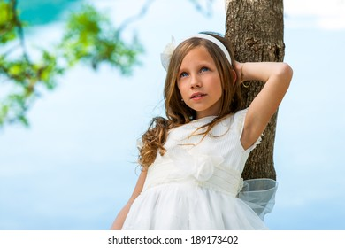 Close up portrait of cute girl in white dress against tree.