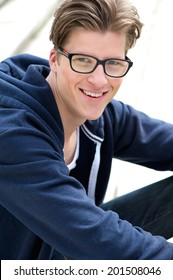 Close up portrait of a cute guy smiling with glasses