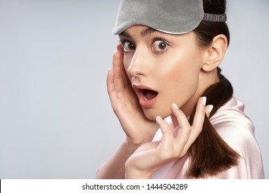 Close up portrait of cute lady with sleep mask on her forehead looking at camera with astonished expression. Isolated on light blue background