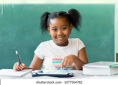 Close up portrait of cute little african student writing and working at desk with digital tablet. Ponytailed kid smiling with blank black board in background.