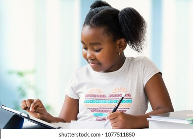 Close up portrait of cute little african girl doing home work at desk. Ponytailed kid typing on digital tablet and writing with pen on paper.