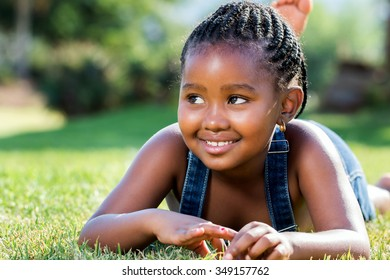 Close up portrait of cute little african girl with braids laying on green grass.