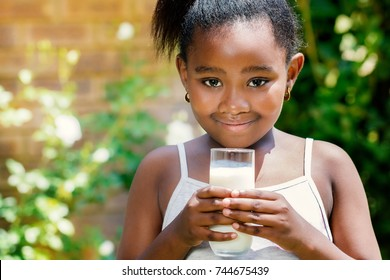 Close up portrait of cute little african girl holding glass with milk in garden.