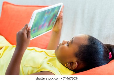 Close up portrait of cute little african girl playing with digital tablet. Kid laying on couch looking at movie.